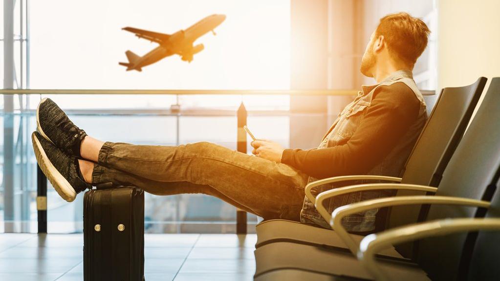 MediaAnalyzer-Studie-Sommerzeit-ist-Reisezeit-Klimaschutz-Mann-Flughafen-Flugzeug